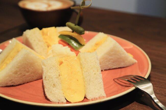『俺のBakery&Cafe』の「厚焼きたまごサンドイッチ」とカフェラテ