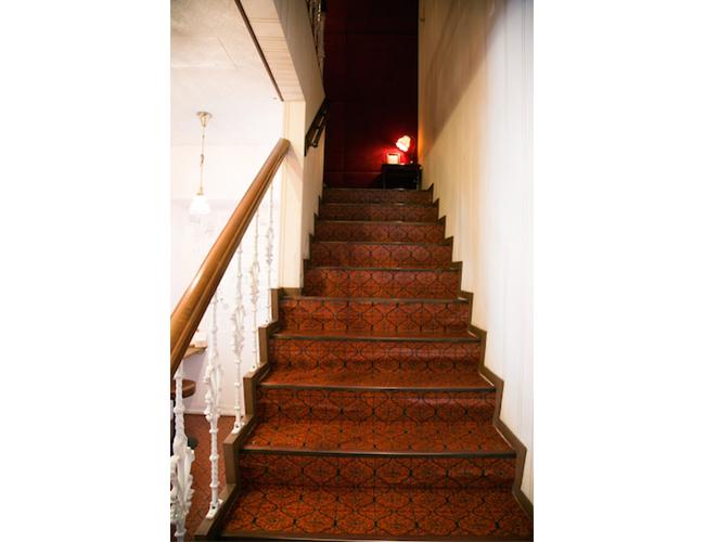 2階へ続く階段。床のクロスは写真館当時のまま