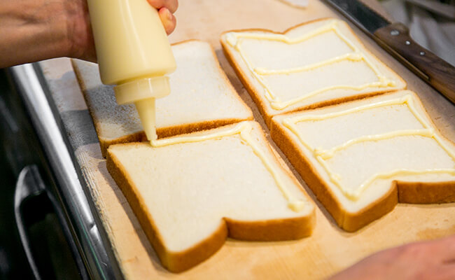 食パンの端にマヨネーズをのせる様子