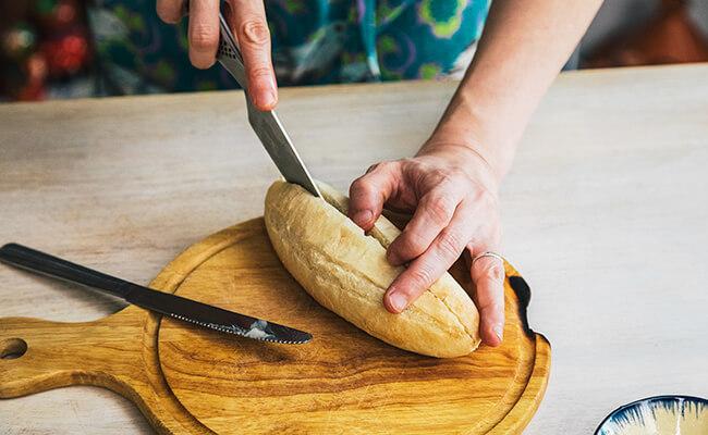 フランスパンに切れ目を入れる様子