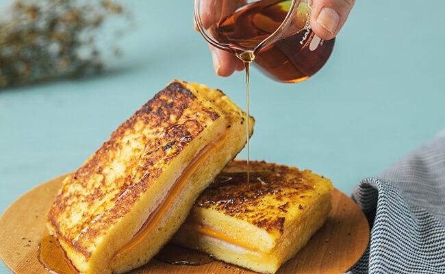 ハムとチーズのフレンチトーストにメイプルシロップをかける様子