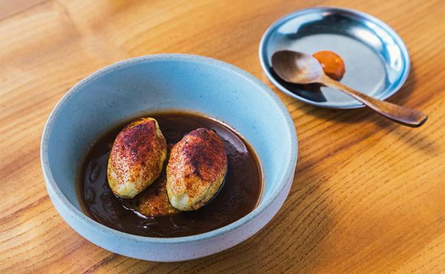 「魚介のすり身とブイヤベース」。リヨンの郷土料理「クネル」の下に焼きリゾットが敷かれていて、ひと口味わうごとに奥深い風味が広がります。ハリッサで味変も楽しめます!